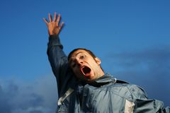 Man shouting. Crazy shouting young man outdoors over blue sky Royalty Free Stock Images
