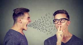 Men having conflict trying to solve problem. Man shouting with abusive words at another man trying to ask for silence Stock Image