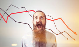 Man shouting at declining graphs, toned. Shouting man with long beard is standing near gray wall with three declining graphs. Concept of crisis, toned image Stock Images