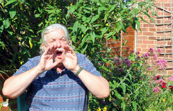 Man shouting. An elderly man cupping his hands together to his mouth and shouting Royalty Free Stock Photos