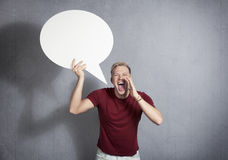 Man shouting  with empty speech ballon in hand. Royalty Free Stock Photos