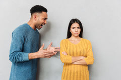 Man shouting at his girlfriend. Angry african men shouting at his upset girlfriend isolated stock photo