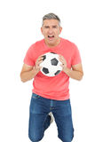Man shouting and holding a soccer ball Royalty Free Stock Photo