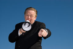 Man shouting through loud speaker. Horizontal shot of a business man wearing a suit shouting through a megaphone and pointing at the camera. Blue sky is the Stock Photos