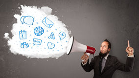 Man shouting into loudspeaker and modern blue icons and symbols Stock Photos