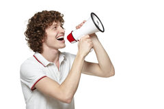 Man shouting into megaphone. Happy man making announcement over a megaphone against white background Royalty Free Stock Image