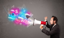Man shouting into megaphone and abstract text and balloons come Royalty Free Stock Photo