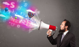 Man shouting into megaphone and abstract text and balloons come Stock Image
