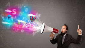 Man shouting into megaphone and abstract text and balloons come Royalty Free Stock Photos
