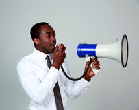 Man shouting through a megaphone. African man shouting through a megaphone on gray background Stock Photos