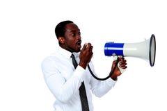 Man shouting through a megaphone. African man shouting through a megaphone isolated on a white background Royalty Free Stock Photo