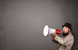 Man shouting into megaphone on copy space background Royalty Free Stock Image