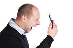 Man shouting at the mobile phone. Mid adult balding man shouting at the mobile phone Stock Image
