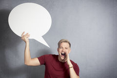Man shouting news with speech ballon in hand. Fantastic news: Joyful man shouting great news while holding white blank speech bubble with space for text Stock Photos