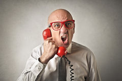 Man shouting at the phone. Fashion businessman screaming to someone on the phone Royalty Free Stock Images
