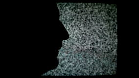 Man shouting on TV. Silhouette of unshaven male in front of static TV noise background stock footage