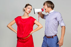 Man shouting at woman. Young men shouting at girlfriend in megaphone. Over grey background Royalty Free Stock Photos
