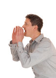Man shouting. A young man holding his hands on his mouths and shouting with his Royalty Free Stock Photo