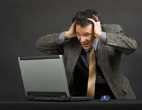 Man shouts with despair looking at computer screen. The young man shouts with despair looking at the computer screen Stock Photo