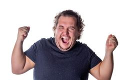Man shouts, lifting his hands up into fists. Excited man celebrating success with hands raised against white background royalty free stock photography