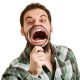 A man shouts. See crooked teeth through a magnifying glass. Stock Photo