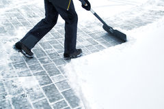 Man with shovel cleaning snow at day light Stock Photography