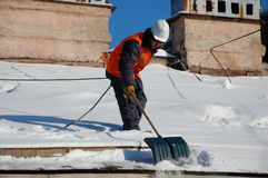 A man with a shovel removes snow from a roof Stock Photos