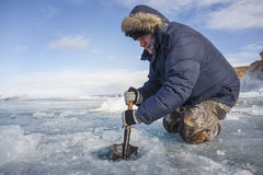 A man with a shovel splits the frozen ice in lake Stock Photography