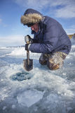 A man with a shovel splits the frozen ice in lake Stock Images