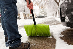 Man  shoveling and removing snow in front of his house in the suburb Royalty Free Stock Photography