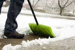Man  shoveling and removing snow in front of his house in the suburb Royalty Free Stock Photos