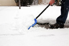 Man  shoveling and removing snow in front of his house in the suburb Royalty Free Stock Images