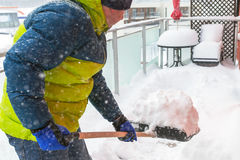 Man shoveling the show on the terrace Stock Photos