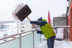 Man shoveling the show on the terrace Stock Images