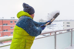 Man shoveling the show on the terrace Royalty Free Stock Photos