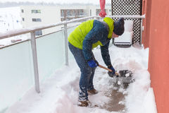 Man shoveling the show on the terrace Royalty Free Stock Images