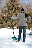 Man Shoveling Snow. A man holds his snow shovel while looking at the work ahead of him Royalty Free Stock Photos