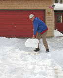 Man shoveling snow. Upbeat man shoveling snow from driveway royalty free stock image