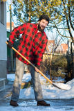 Man shoveling snow. Bearded man shoveling snow in a checked shirt Royalty Free Stock Images