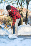 Man shoveling snow. Bearded man shoveling snow in a checked shirt Stock Image