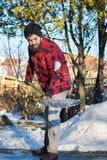 Man shoveling snow. Bearded man shoveling snow in a checked shirt Royalty Free Stock Photography