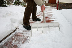 Man shoveling snow at a footpath royalty free stock photography