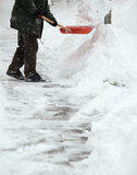 Man shoveling snow from the sidewalk. In front of his house after a heavy snowfall in a city Royalty Free Stock Images