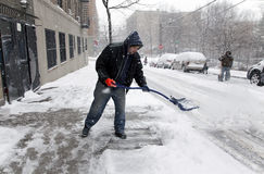 Man shoveling during snow storm in New York Stock Image