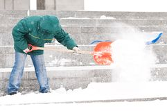 Man shoveling winter snow. Communal services worker in uniform shoveling snow in winter snowstorm Stock Images