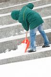 Man shoveling winter snow. Communal services worker in uniform shoveling snow in winter snowstorm Royalty Free Stock Photography