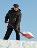 Man shovelling snow with a red shovel Royalty Free Stock Image