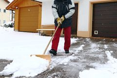 A man shovels snow in front of the garages.  stock photos