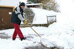 A man shovels snow in front of the garages.  Stock Photography