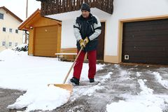 A man shovels snow in front of the garages.  stock photo